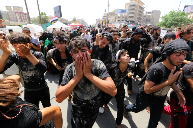 Shiite pilgrims beat themselves and cover themselves with mud as they march toward the Imam Mousa al-Kazim shrine to commemorate the anniversary of the imam's death in Baghdad, Iraq, Monday, May 11, 2015. The anniversary of the 8th-century imam's death draws tens of thousands of Shiites from all walks to converge on his golden-domed shrine in northern Baghdad. (Photo by Hadi Mizban/AP Photo)