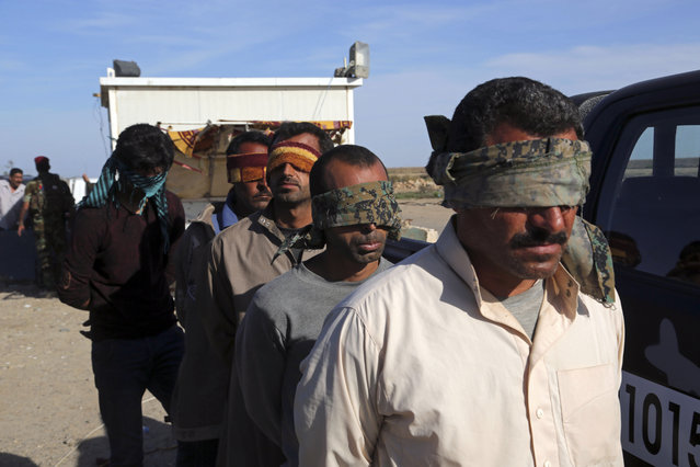 Suspected members of the Islamic State group wait to be taken for interrogation after being found among civilians returning to Ramadi for the first time since the city was taken back by Iraqi government forces earlier this year, in Ramadi, Iraq, Sunday, April 3, 2016. (Photo by Khalid Mohammed/AP Photo)