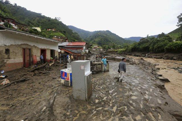 Residents stand in front of the ruins of houses, after a landslide close to the municipality of Salgar in Antioquia department, Colombia May 19, 2015. (Photo by Jose Miguel Gomez/Reuters)