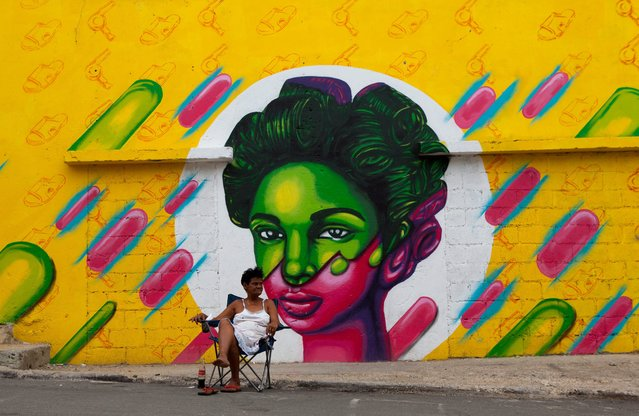 A woman rests in a chair next to a grafitti at Santa Barbara neighborhood in the Colnian Zone, in Santo Domingo, Dominican Republic, 19 May 2015. (Photo by Orlando Barria/EPA)