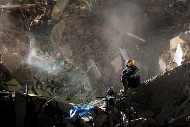 A rescue worker searches at the site after a three-storey residential building collapsed in Shanghai, China, April 11, 2016. (Photo by Aly Song/Reuters)