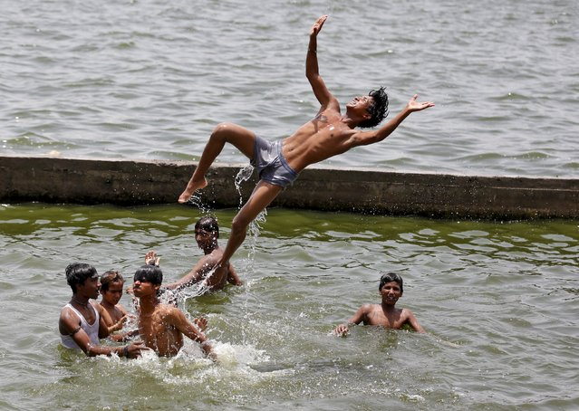 Boys cool off themselves in the waters of the river Sabarmati on a hot summer day in Ahmedabad, India, May 24, 2015. (Photo by Amit Dave/Reuters)