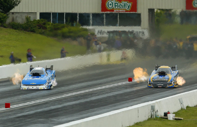 Funny Car drivers John Force, left, and Matt Hagen tear down the track during the semifinals of the 2015 NHRA Kansas Nationals on Sunday, May 24, 2015, at Heartland Park in Topeka, Kan. (Photo by Chris Neal/The Topeka Capital-Journal via AP Photo)