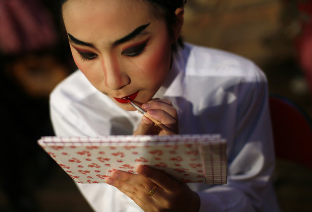 """In this Tuesday Aug. 20, 2013 photo, a Chinese opera actress puts on make-up at a makeshift theater during the """"Hungry Ghost Festival"""" in Hong Kong. (Photo by Vincent Yu/AP Photo)"""