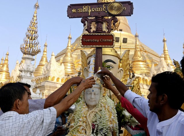 Burmese people pour water on a Buddha statue at the Shwedagon pagoda in Yangon, Myanmar, 17 April 2016. Myanmar people celebrate the New Year of the Burmese calendar by going to pagodas, donating food, freeing birds or fish and paying their respects to the elderly. (Photo by Nyein Chan Naing/EPA)