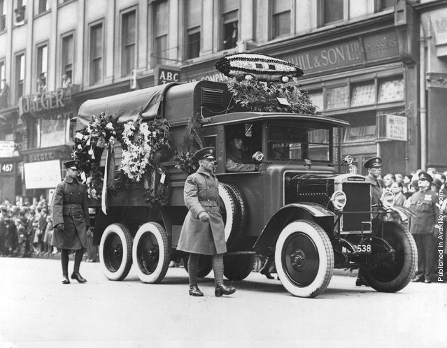 1930: An RAF lorries decorated with flowers including a model of the R101 airship, in a funeral  procession for victims of the R 101 airship crash, watched by large crowds
