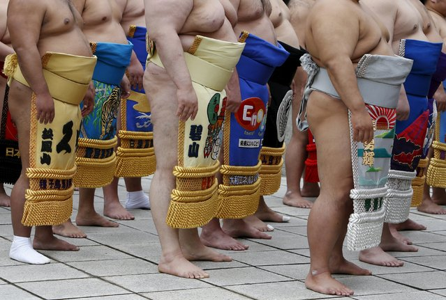 """Sumo wrestlers line up as they pray before the start of the annual """"Honozumo"""" ceremonial sumo tournament dedicated to the Yasukuni Shrine in Tokyo, Japan, April 18, 2016. (Photo by Yuya Shino/Reuters)"""