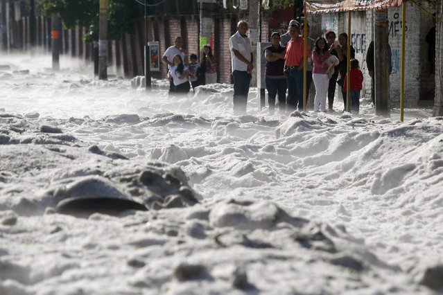 People remain on the sidewalk of a street covered with hail in the eastern area of Guadalajara, Jalisco state, Mexico, on June 30, 2019. The accumulation of hail in the streets of Guadalajara buried vehicles and damaged homes. (Photo by Ulises Ruiz/AFP Photo)