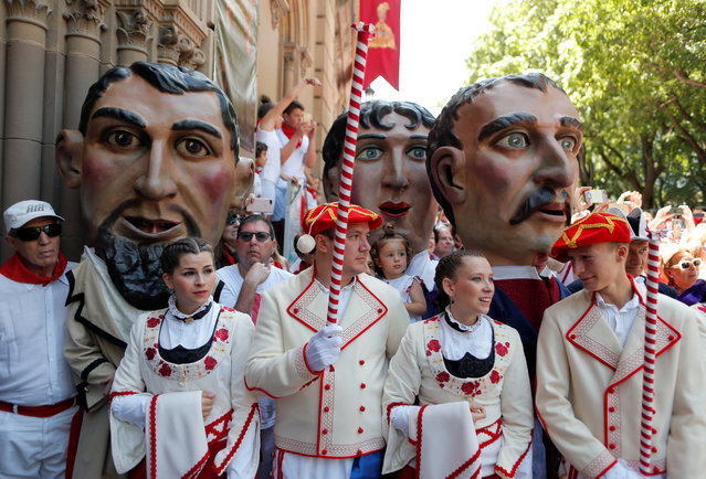 """""""Cabezudos"""" (Big heads) and dancers take part in a procession of the Saints Day after the first running of the bulls at the San Fermin festival in Pamplona, Spain, July 7, 2019. (Photo by Jon Nazca/Reuters)"""