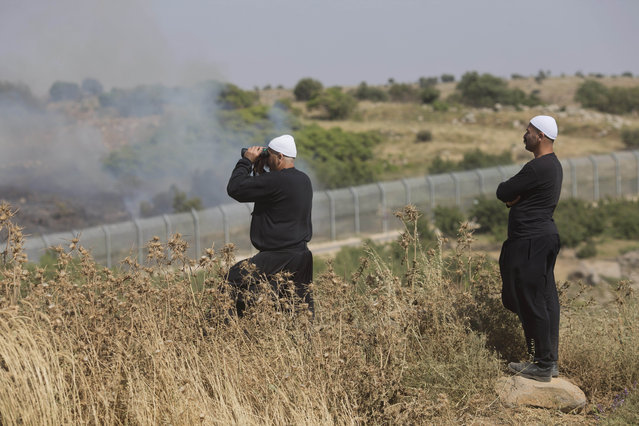 Members of Israel's Druze minority watch fighting between forces loyal to Syrian President Bashar Assad and rebels in the Druze village of Khader in Syria, from the Israeli controlled Golan Heights, Tuesday, June 16, 2015. Battles are raging in the Druze village of Khader near the Israeli frontier. As many as 20 members of the Druze minority sect were killed last week, the deadliest violence against the Druze since Syria's conflict started in March 2011, sparking fears of a massacre against the sect. (AP Photo/Ariel Schalit)