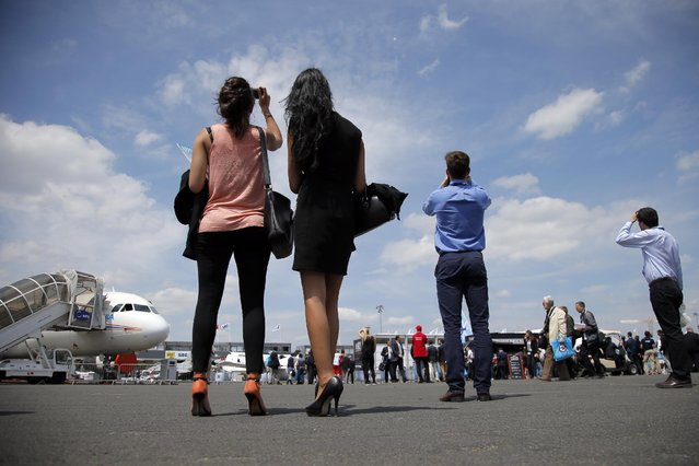 Onlookers look for the demonstration flights of the Paris Air Show,  in Le Bourget airport, north of Paris, Tuesday, June 16, 2015. Some 300,000 aviation professionals and spectators are expected at this weekends Paris Air Show, coming from around the world to make business deals and see dramatic displays of aeronautic prowess and the latest air and space technology. (AP Photo/Francois Mori)
