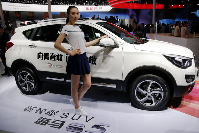 A girl poses by Haima S5 SUV at the Haima Automobile Group booth during the Auto China 2016 auto show in Beijing April 26, 2016. (Photo by Kim Kyung-Hoon/Reuters)