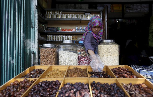 A shopkeeper prepares dates, a popular fruit for breaking the fast during the holy month of Ramadan, in Jakarta, Indonesia, June 25, 2015. (Photo by Nyimas Laula/Reuters)