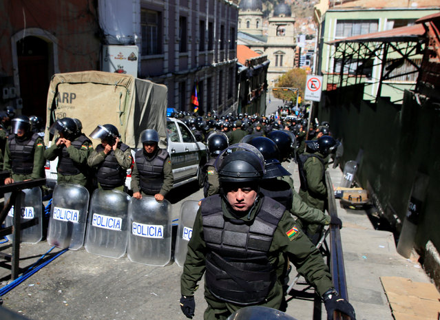 Riot police guard one of the entrances to Murillo square, during a protest by people with physical disabilities demanding the government to increase their monthly disability subsidy, in La Paz, Bolivia, April 29, 2016. (Photo by David Mercado/Reuters)