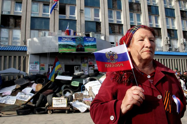 An elderly woman with Russian flag poses in front of the occupied security service building in Lugansk, Ukraine, 16 April 2014. (Photo by Zurab Kurtsikidze/EPA)