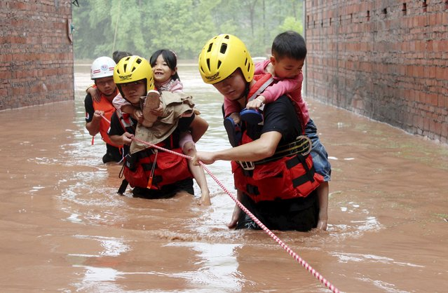 Rescuers carry children on their back as they walk among floodwaters after heavy rainfall hit Dazhou, Sichuan province, China, June 25, 2015. (Photo by Reuters/China Daily)
