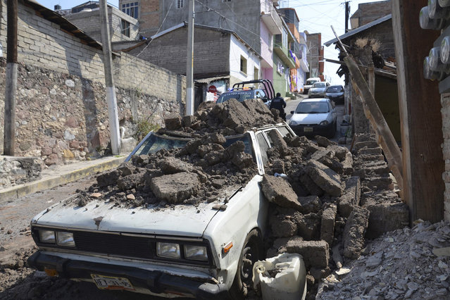 A parked car suffered damage when a adobe wall collapsed on it after a strong earthquake shook Chilpancingo, Mexico, Friday morning, April 18, 2014. A powerful magnitude-7.2 earthquake shook central and southern Mexico but there were no early reports of major damage or casualties. (Photo by Alejandrino Gonzalez/AP Photo)