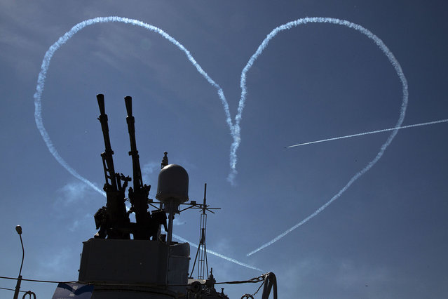 """L-39 jets of the """"Russkiye Vityasy"""" aerobatic team create by smoke a heart pierced by an arrow during an air show at the International Maritime Defence show in St.Petersburg, Russia, Thursday, July 2, 2015. (Photo by Dmitry Lovetsky/AP Photo)"""