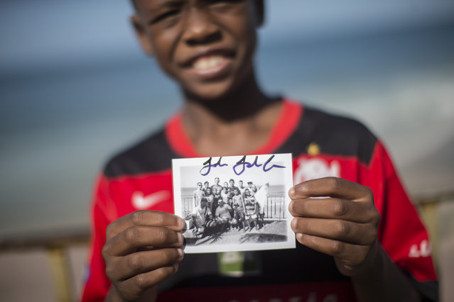 In this May 21, 2015 photo, Christian da Conceicao, 11, shows a signed polaroid photo of him and friends with U.S. surfer John John Florence at Sao Conrado beach in Rio de Janeiro, Brazil. Everyday barefoot boys hustle down the inclined alleyways of the Rio de Janeiro slums they call home, surf boards under their arms. They head to nearby Sao Conrado or Arpoador beach, where they catch waves and momentarily leave their impoverished lives behind. (Photo by Felipe Dana/AP Photo)