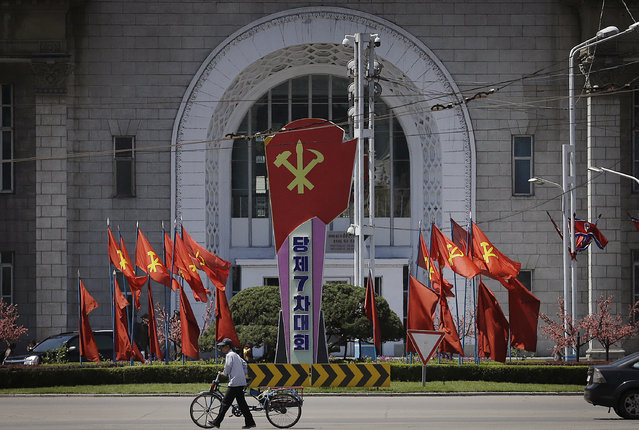 A man pushes his bicycle past the Pyongyang train station which is decorated with the ruling Workers' Party flags Sunday, May 8, 2016, in Pyongyang, North Korea. North Korean leader Kim Jong Un said during a critical ruling party congress that his country will not use its nuclear weapons first unless its sovereignty is invaded. He also announced a five-year plan starting this year to develop the North's dismal economy and identified improving the country's power supply and increasing its agricultural and light-manufacturing production as the critical parts of the program, state media reported. (Photo by Wong Maye-E/AP Photo)