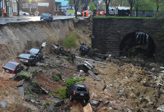 One lane of the East 26th Street between North Charles and North St. Paul streets in Baltimore collapsed about 4 p.m. and slid down an embankment leading to the tracks below, washing away cars and flooding the CSX railroad, as a massive storm system dropped heavy rains on the D.C. region. (Photo by Jonathan Newton/The Washington Post)