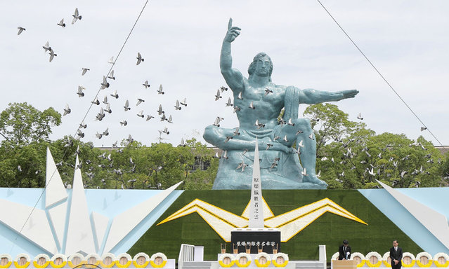 Doves fly around the Peace Statue during a memorial service to mark the 74th anniversary of the atomic bombing at the Peace Memorial Park in Nagasaki on August 9, 2019. (Photo by JIJI Press/AFP Photo)