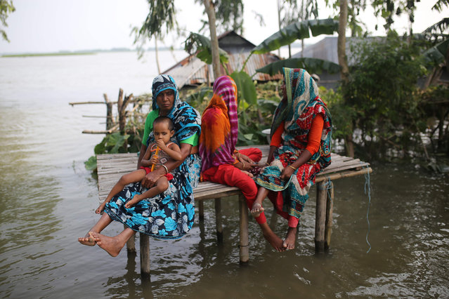 In this picture taken on 16 July, 2019, Bangladeshi people sit in a bamboo platform as they look at flood waters in Kurigram district, in the northern part of Bangladesh. Survivors scrambled for higher ground as torrential monsoon rains swept away homes and triggered landslides across South Asia on July 16, with millions of people affected and at least 180 dead, officials said. (Photo by Rehman Asad/AFP Photo)