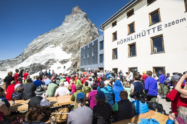 Guests gather on the terrace of Hoernli hut in front of the Matterhorn mountain, Switzerland, July 14, 2015 as Zermatt celebrates 150 years since the first ascent of the Matterhorn mountain. On July 14, 1865, the British climber Edward Whymper reached the peak of the Matterhorn (4,478 metres above sea level) together with his rope team. (Photo by Dominic Steinmann/EPA)