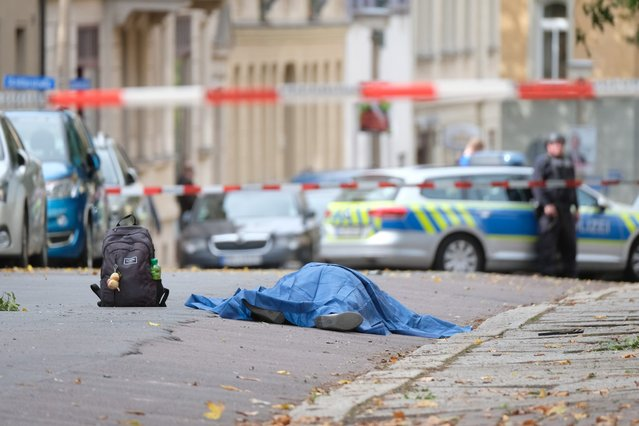 "A body laying in the street is covered as police block the area around the site of a shooting in Halle an der Saale, eastern Germany, on October 9, 2019. At least two people were killed in a shooting on a street in the German city of Halle, police said, adding that the perpetrators were on the run. ""Early indications show that two people were killed in Halle. Several shots were fired. The suspected perpetrators fled in a car"", said police on Twitter, urging residents in the area to stay indoors. (Photo by Sebastian Willnow/dpa/AFP Photo)"