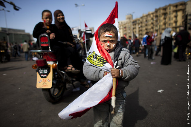 An egyptian boy wears a egyprian national flag at Tharir Square