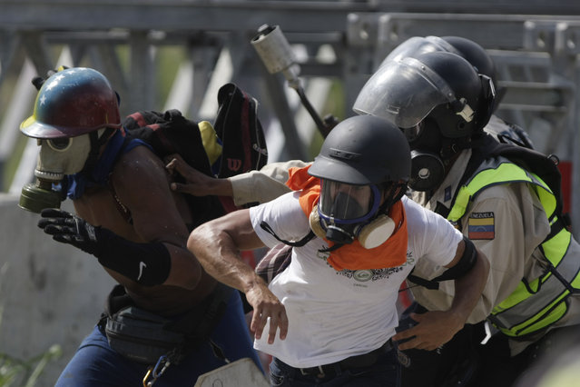 Anti-government protesters run from police during an opposition march in Caracas, Venezuela, Wednesday, May 10, 2017. (Photo by Fernando Llano/AP Photo)