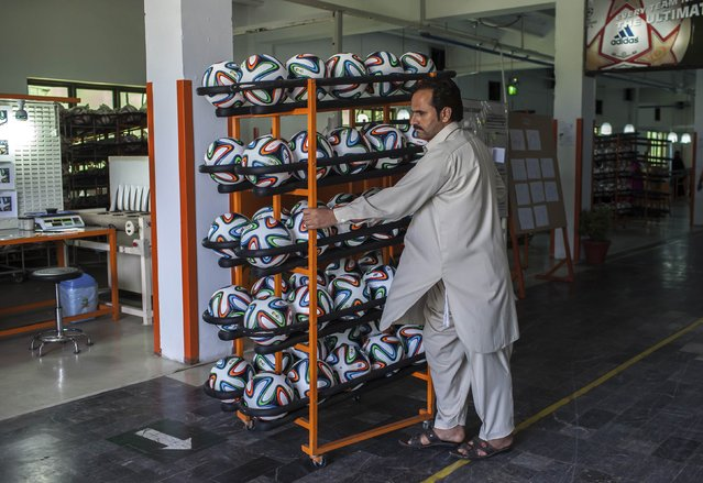 An employee takes finished balls out of the production area inside the soccer ball factory that produces official match balls for the 2014 World Cup in Brazil, in Sialkot, Punjab province May 16, 2014. (Photo by Sara Farid/Reuters)