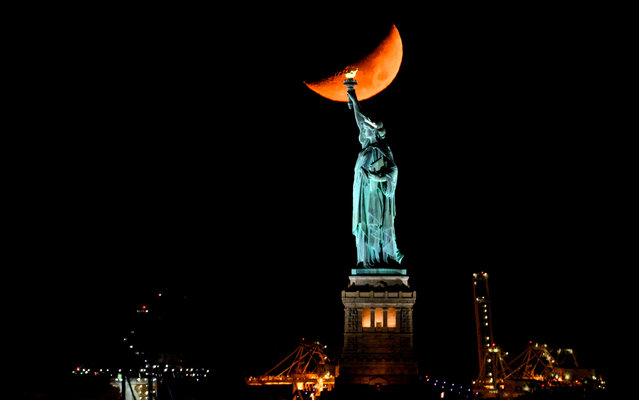 The moon sets behind the Statue of Liberty on November 2, 2019 in New York City. (Photo by Johannes Eisele/AFP Photo)