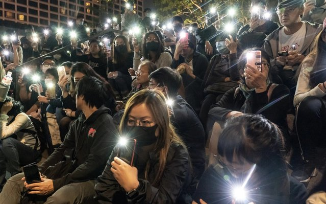 "Pro-democracy supporters hold their phone's flashlight in a rally to show support for students at The Hong Kong Poytechnic University on November 19, 2019 in Hong Kong, China. Anti-government protesters armed with bricks, firebombs, and bows and arrows fought with the police at university campuses over the past week as demonstrations in Hong Kong stretched into its sixth month with demands for an independent inquiry into police brutality, the retraction of the word ""riot"" to describe the rallies, and genuine universal suffrage. (Photo by Anthony Kwan/Getty Images)"