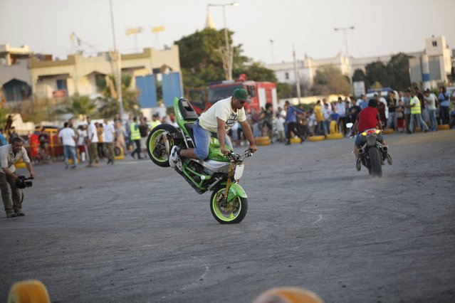 """A youth riding a motorcycle performs a stunt during the """"Peace and Security"""" event in Tripoli, Libya July 23, 2015. The event was organised by the Abu Saleem police department to give enthusiasts a venue to perform motor stunts. (Photo by Ismail Zitouny/Reuters)"""