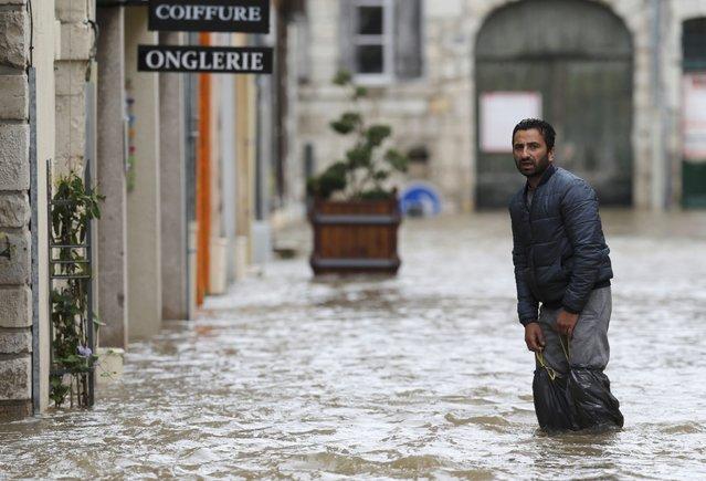 A man walks in a flooded street in Montargis in the Loiret, following heavy rain in France June 1, 2016. (Photo by Christian Hartmann/Reuters)