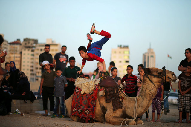 Mohamad al-Sheikh, 12, demonstrates acrobatics skills on a beach in Gaza City June 2, 2016. (Photo by Mohammed Salem/Reuters)