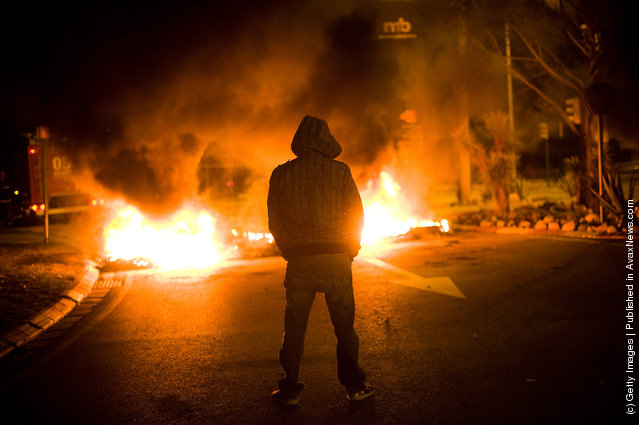 A demonstrator stands next to a barricade of burning tires at the main entrance of Mercabarna, the biggest wholesale market of Barcelona, on March 29, 2012 in Barcelona, Spain