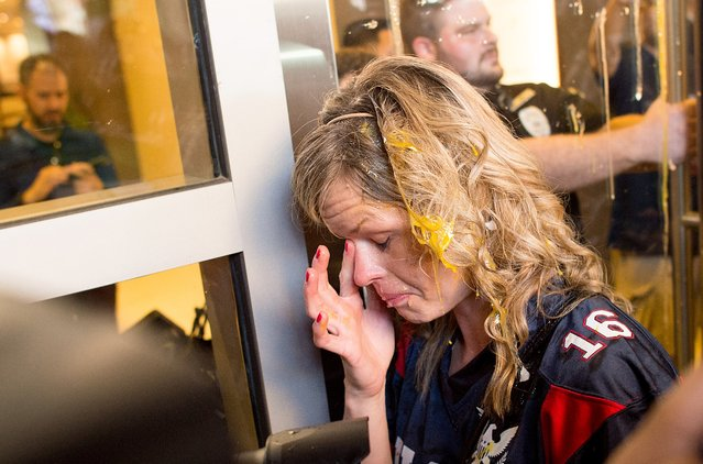 A woman wipes egg off her face after being pursued by protesters while leaving Republican presidential candidate Donald Trump's campaign rally on Thursday, June 2, 2016, in San Jose, Calif. A group of protesters attacked Trump supporters who were leaving the presidential candidate's rally in San Jose on Thursday night. A dozen or more people were punched, at least one person was pelted with an egg and Trump hats grabbed from supporters were set on fire on the ground.  (Photo by Noah Berger/AP Photo)