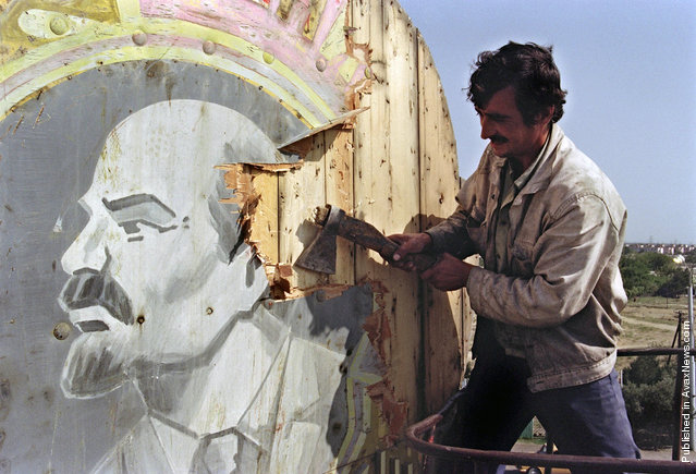 A Baku resident uses an axe to hack apart a placard showing a portrait of Russian Bolshevik revolutionary leader Vladimir Lenin, on September 21, 1991. Azerbaijan was proclaimed a Soviet Socialist Republic by Soviet Union in 1920. The Azeri National Council voted for its declaration of independence in 1991