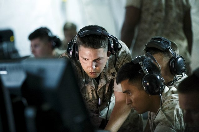 """Marines from the USMC Marine Air Control Squadron 1 monitors and relays information from the AN/TPS-59 air search radar system in the Tactical Air Operations Center (TAOC) during """"Black Dart"""", a live-fly, live fire demonstration of 55 unmanned aerial vehicles, or drones, at Naval Base Ventura County Sea Range, Point Mugu, near Oxnard, California July 31, 2015. (Photo by Patrick T. Fallon/Reuters)"""