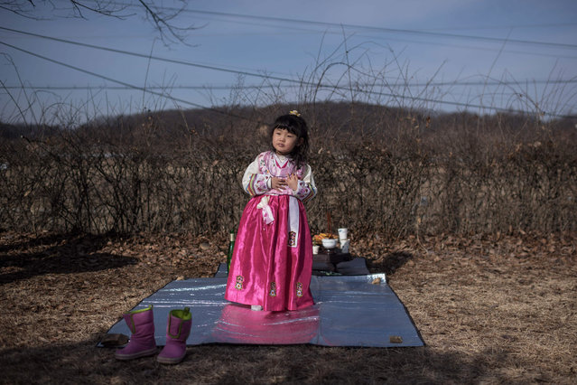 Park Yeon-Hee stands before an altar facing the North, to which prayers are offered for relatives and ancestors separated by the Korean war, near the Demilitarized Zone (DMZ) separating North and South Korea in Imjingak on January 28, 2017. On the frozen banks of the Imjin river, South Koreans divided from their families decades ago by war gathered to pay respects to their ancestors. According to tradition, Korean ceremonies for the lunar new year must be carried out by the eldest son – they lined up before an altar piled with offerings of rice cakes, fruit and fish. (Photo by Ed Jones/AFP Photo)