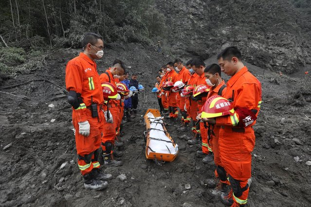 Rescue workers stand in silent tribute before evacuating a body from the site of a landslide in the village of Xinmo, Mao County, Sichuan Province, China June 25, 2017. (Photo by Reuters/Stringer)