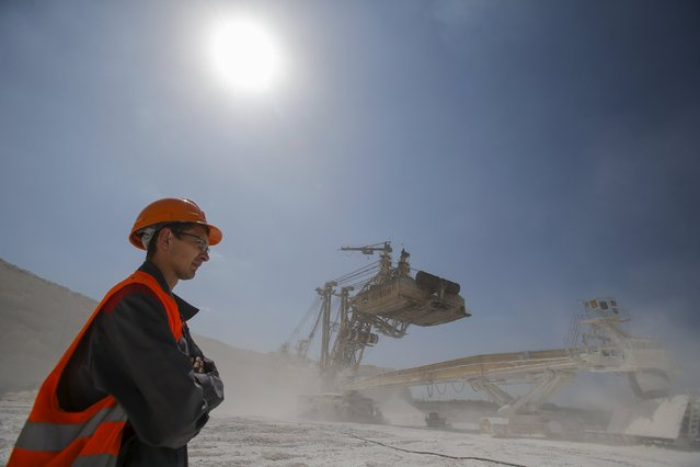 An employee stands near a rotary dredge working at an open-cast iron ore mine of the Stoilensky mining and concentration plant (GOK), owned by the Novolipetsk (NLMK) steel mill, in the city of Stary Oskol in Belgorod region, Russia, August 4, 2015. (Photo by Maxim Shemetov/Reuters)