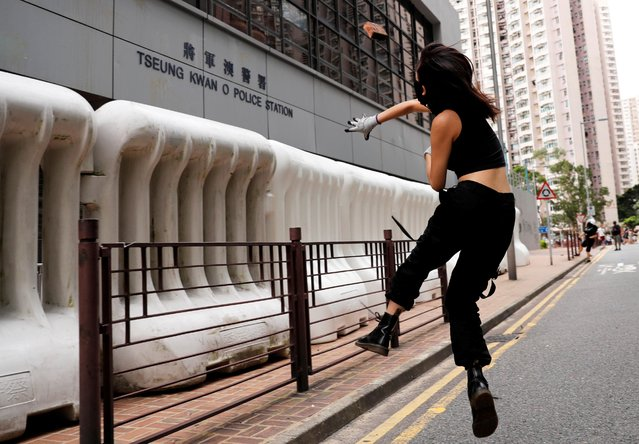 An anti-extradition bill protester throws a stone at a police station in Tseung Kwan O residential district, in Hong Kong, China, August 4, 2019. (Photo by Kim Kyung-Hoon/Reuters)