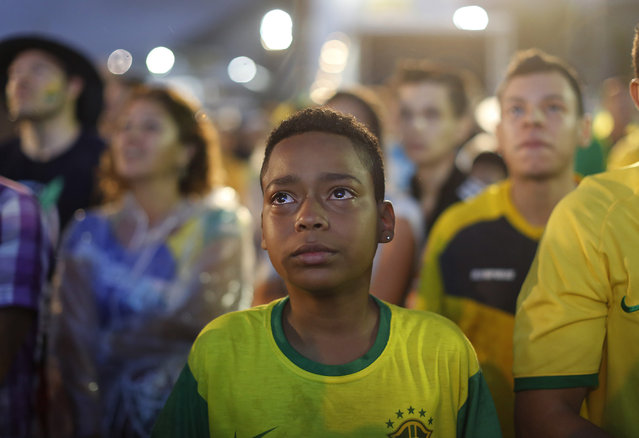 A Brazil soccer fan cries as he watches his team get beat during a live telecast of the semi-finals World Cup soccer match between Brazil and Germany, inside the FIFA Fan Fest area on Copacabana beach in Rio de Janeiro, Brazil, Tuesday, July 08, 2014. (Photo by Leo Correa/AP Photo)