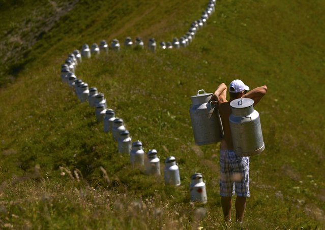 A volunteer carries milk churns as he helps land art artist Gerard Benoit a la Guillaume to form an art installation at the Chenau de Mayen in the resort of Leysin, Switzerland August 7, 2015. (Photo by Denis Balibouse/Reuters)
