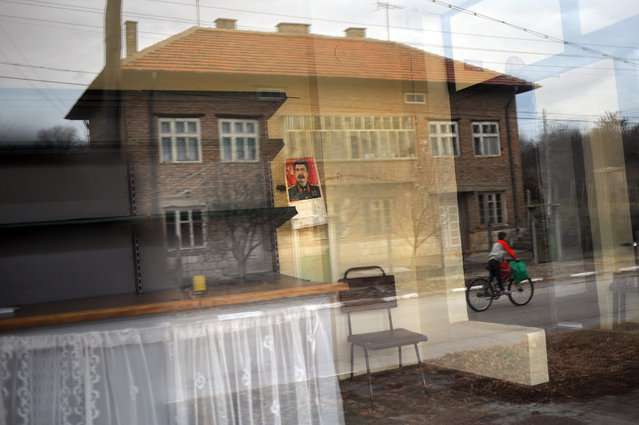 A reflection of a building in the windows of an empty shop bearing the picture of Soviet leader Joseph Stalin