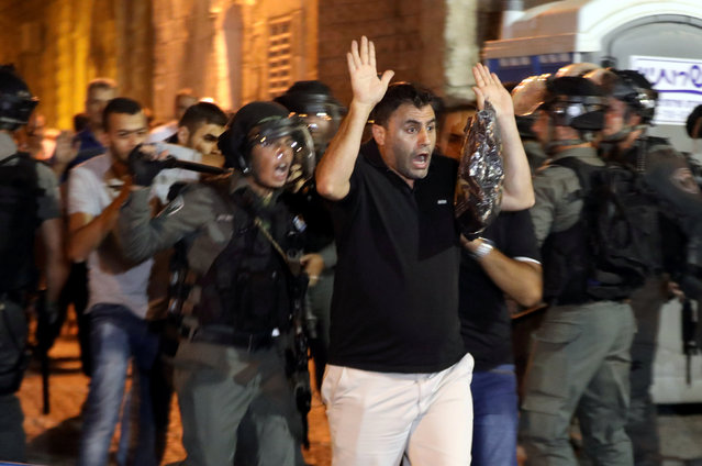 Israeli border police clash with Palestinian men during scuffles that erupted after Palestinians held evening prayers outside the Lion's Gate of Jerusalem's Old City July 18, 2017. (Photo by Ammar Awad/Reuters)