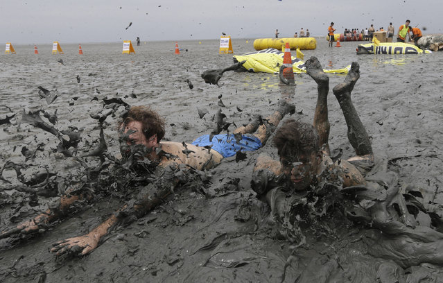 Men slide in the mud during the Boryeong Mud Festival at Daecheon Beach in Boryeong, South Korea, Saturday, July 22, 2017. The 20th annual mud festival features mud wrestling and mud sliding. (Photo by Ahn Young-joon/AP Photo)